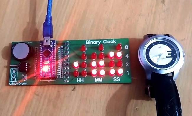 """crisstel.ro Arduino – ceas binar Ce este ceasul binar ? Spre deosebire de un ceas obișnuit cu numere sau cu limbă mai există o variantă de ceasuri ce reprezinta ora și minutul în format binar Un ceas de timp real (RTC) LED-urile ceasului se vor aprinde în funcție de codul binar Dacă în codul binar vei întâlni un """"1"""" logic atunci LED-ul va sta aprins sau stins dacă este vorba de un """"0"""" logic Ceasul de timp real este un circuit integrat specializat în a menține timpul adică funcționează asemănător cu un ceas RTC-ul este util deoarece placa Arduino nu este destinată pentru a face acest lucru Cum se construiește un ceas binar ? Ceasul se poate alimenta fie dintr-un alimentator extern sau dintr-o baterie Fiecare LED se conectează la pinii digitali ai plăcii Arduino Nu uita ca fiecare LED se înseriază cu câte o rezistenta de 220 de Ohmi"""